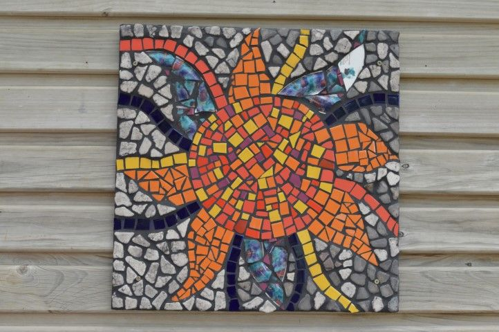 A mosaic made from smashed tiles and a dinner plate.