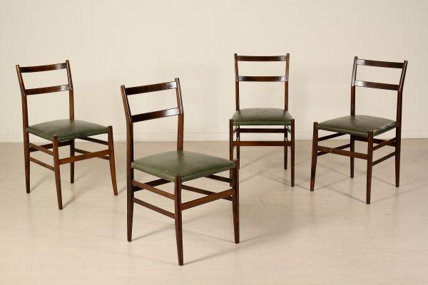 Gruppo di quattro sedie; legno di frassino tinto, seduta in similpelle. Buone condizioni, presentano piccoli segni di usura.