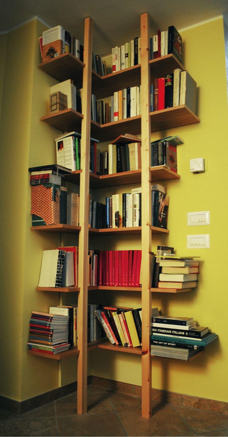 Questa libreria ad angolo è stata progettata al fine di poter sfruttare al massimo la superficie contro le pareti dove poggiano i ripiani. La sensazione che si ha guardandola è di leggerezza e di sospensione.