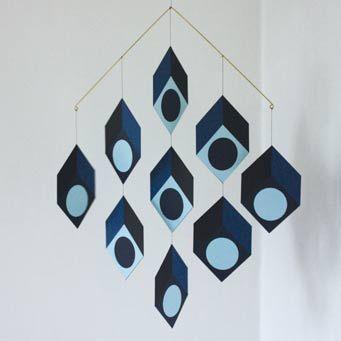 Dekorativ uro i blå fra fynske Livingly. Cubillusion er en hyldest til 1960′ernes Op art, som eksperimenterede med optiske virkemidler. Selvom elementerne i denne uro er flade, snydes øjet til at se enten det indvendige eller udvendige af rumlige kubiske former.  Uroen er lavet af papir af hjemmearbejdere på Fyn. #opart#klassisk#uro#mobile#livingly#designbutik