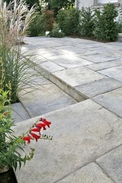 Dalles indémodables  Ces dalles de pierre reconstituée, antidérapantes et ingélives présentent une surface feuilletée. Leur teinte grise se fond dans toutes les ambiances, classiques ou plus contemporaines.