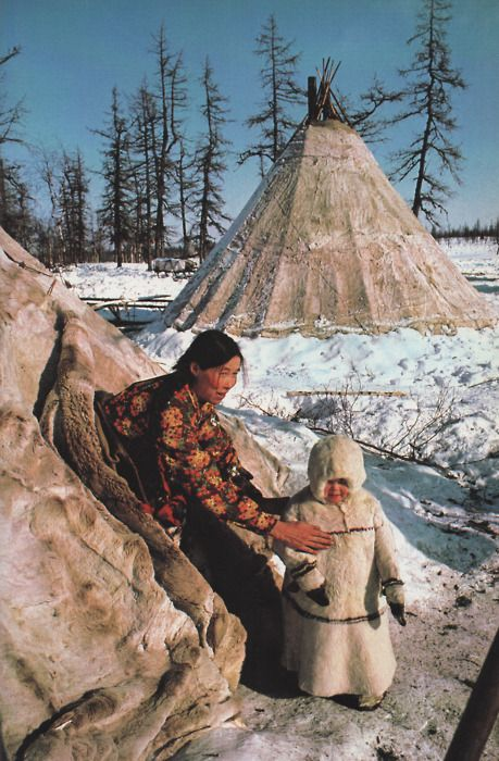 'Warmed by fur & a mother's loving touch, a child ventures from the family`s tent a reindeer herders' camp near Salekhard, in the Soviet Arctic / Photograph by Dean Conger