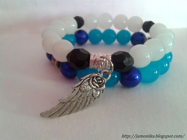 Bransoletka z białych szklanych koralików i plastikowych czarnych, do tego metalowa przekładka z zawieszką w kształcie skrzydła.
