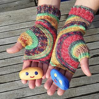 These fingerless gloves form a circle shape around the thumb. They are knitted without breaking the yarn, so there are only two ends to weave in per mitt. The pattern is written that the mitts can be adjusted to fit different hand sizes. The circle shape shows best when using self striping yarn.