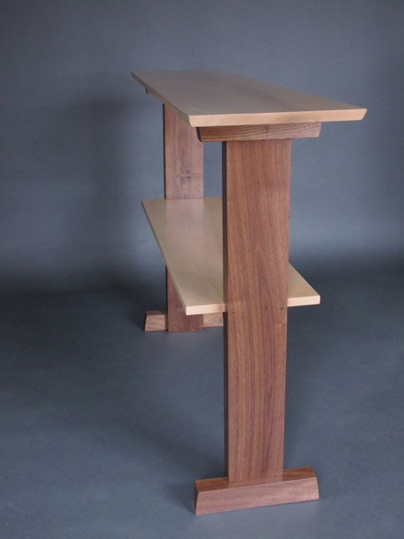 This elegant wood console table is a narrow table design for your hall table, entry table or sofa table. The shelf provides a space for displaying art, family photos or a small library collection. The unique style of the narrow solid leg and the inset shelf makes a refined modern statement for your home decor.  -The shelf is cut into the legs for an interesting joinery detail. -The feet add stability to the narrow table -The velvet touch, hand rubbed finish enhances the beauty of the natural…