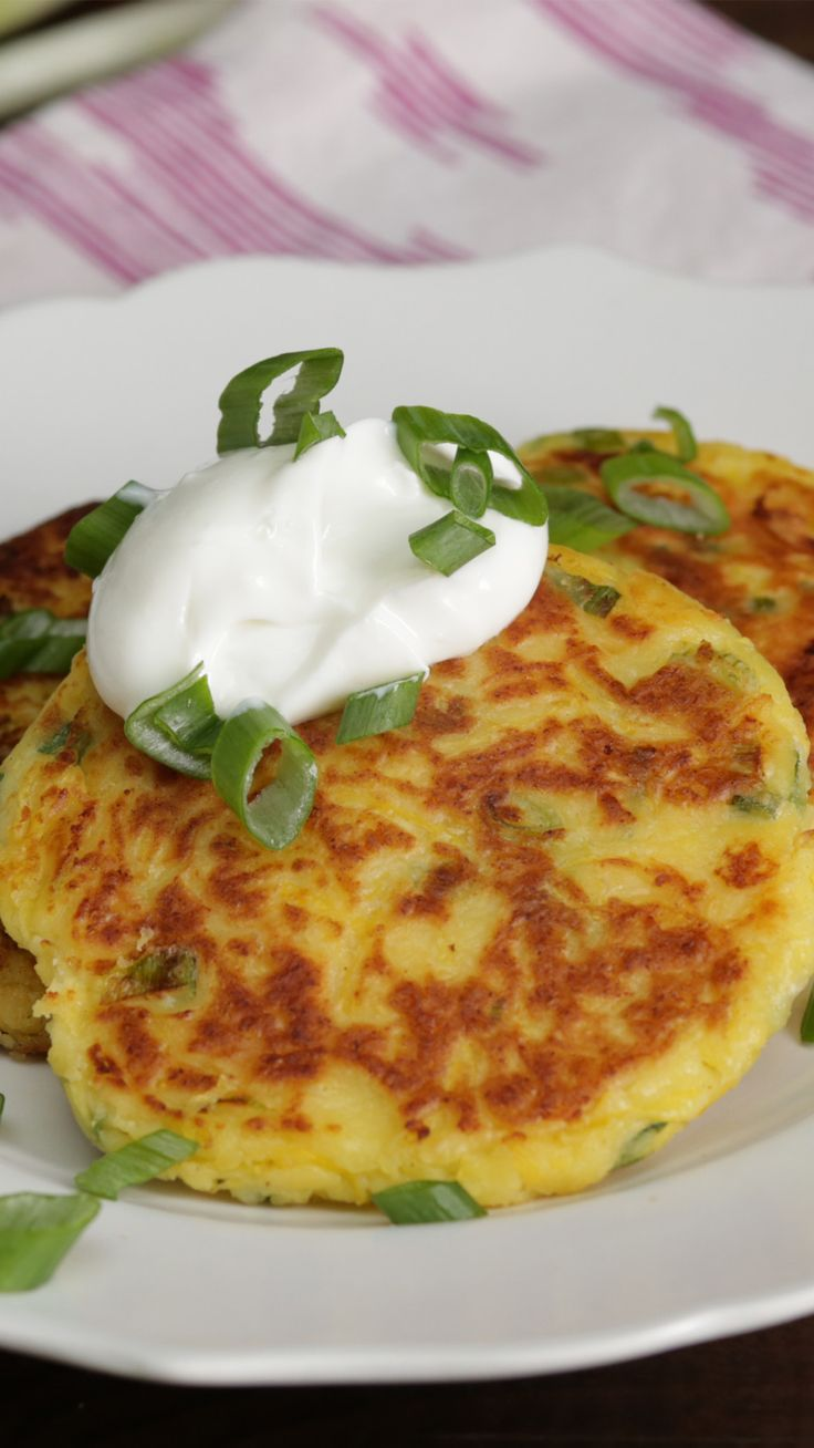 Recipe with video instructions: How to make spaghetti squash fritters. Ingredients: 3 cups spaghetti squash, cooked, ½ cup flour, 1 cup whole milk ricotta, drained, ½ cup grated Parmesan, 2 eggs, 3 green onions, chopped, Salt and pepper, Oil for frying, Greek yogurt, as garnish, Chopped scallions, as garnish