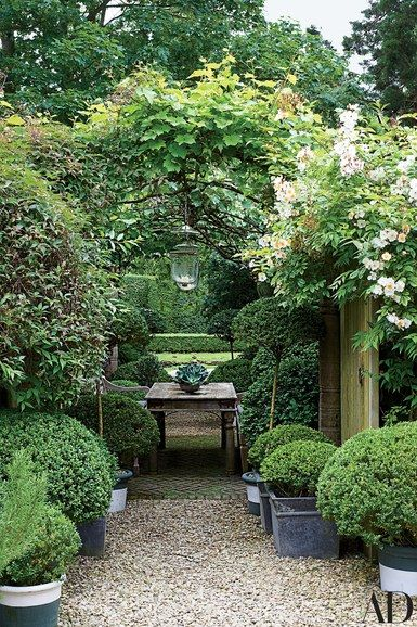 Beneath a vine-clad pergola at the English country manor that designer Anouska Hempel shares with her husband, vintage Indian lanterns dangle above an antique Pakistani table | archdigest.com