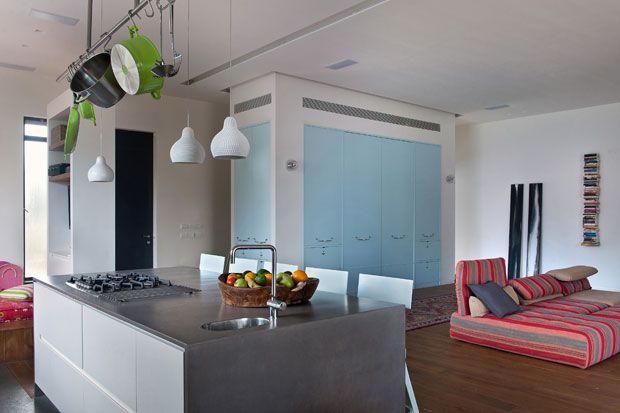 L'elemento con le ante azzurre è stato disegnato su misura dagli architetti. Oltre a nascondere un piccolo studio, separa il living dalle scale che portano al piano di sotto