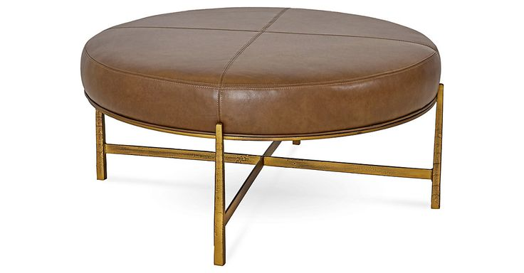 This round ottoman features elegant lines and a clean-lined frame forged of bronze-finished steel. The top is upholstered in supple saddle brown leather and features a plush fill.