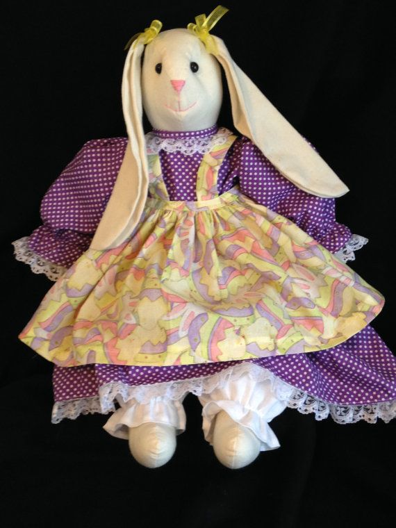"""Handmade Muslin Bunny made with Natural Muslin, 2 Button eyes, A Purple Polka Dot Dress, Yellow Hatched Egg Easter Fabric for the Apron and White Muslin for the Bloomers. They are approx. 20"""" Tall. These can be used for either decorations or for gift giving. Not Recommended to be given to children under the age of 3 because of the button eyes. I have them sewn securely but its never good to take the chance with the little ones. I have several different colors available and will be including…"""