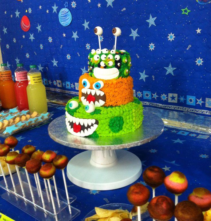 Pastel de tres pisos de alienigenas de buttercream. Forma parte de una mesa dulce temática de fiesta espacial.
