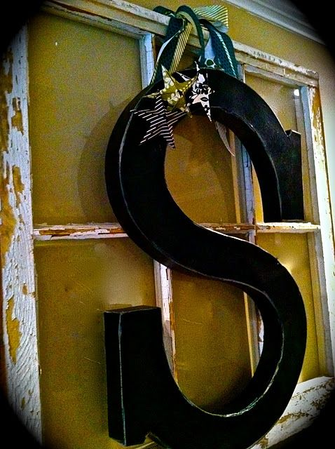 Painted cardboard letter, embellished with homemade paper stars.