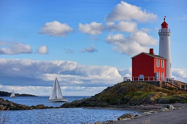 Art prints for sale:  Fisgard Lighthouse historical site in Collwood, BC. Built in 1860, this is the oldest lighthouse on Canada's west coast. Sailboats from the yacht club are passing by in the distance.