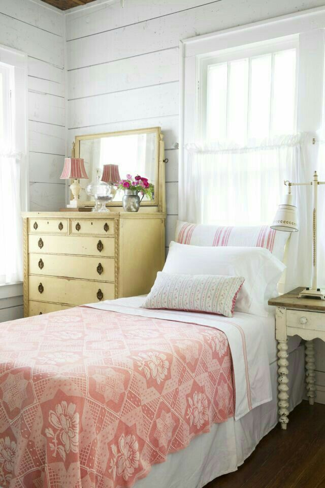 I like the color combination of the yellow dresser with the red bedspread and white shiplap walls.