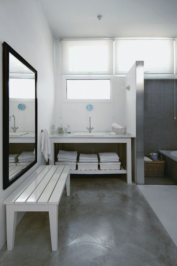 White bench and buffed concrete floors in bathroom.
