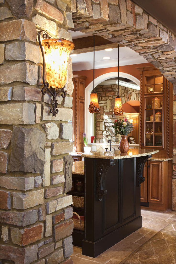 Stone column and arch going to kitchen