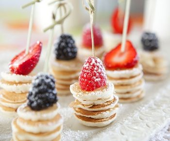 ミニミニパンケーキにベリーをのせるアイディア。粉砂糖のトッピングが繊細できれいなデコレーションです。