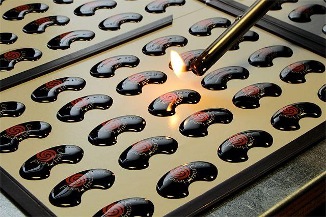 Etichette adesive resinate. Il calore della fiamma rifinisce la resina facendola aderire alla perfezione alla forma dell'etichetta.