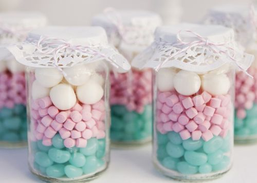 Glass jars covered with doilies and filled with lollies