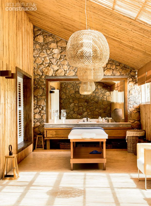 Sala de massagem. Ela tem revestimento de bambu em algumas paredes e no teto. De…
