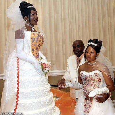 """Obviously someone needed to rein in this woman during the wedding planning. What kind of ego does it require to commission a life-sized replica of yourself in cake? But what really baffles me is this: the details are exact right down to the hair clip, so what the heck is UP with that tacky red rick-rack down the skirt of the cake? """"Sure, we hand-painted a matching bodice-design, copied the make-up and hairstyle, and have identical veils - but then we thought this giant rick-rack would add…"""