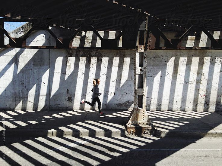 Woman Running In A City Under A Bridge by Laura Austin