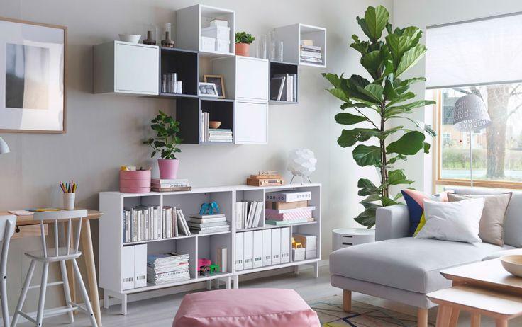 Salon clair avec étagère ouverte blanche, associée à des éléments muraux blancs et gris, certains avec des portes, d'autres sans.