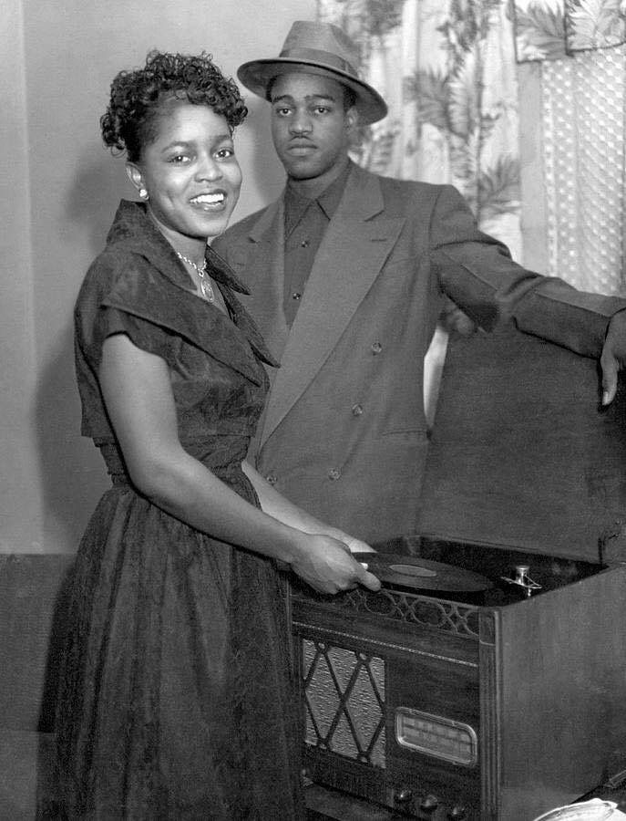 United States c. 1940.A stylish African American couple playing 78 rpm records on a record player. Source: Vintage African American Photography