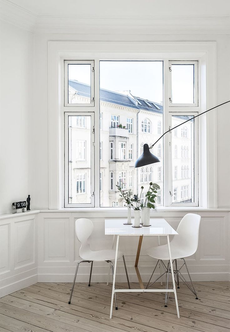 A simple table for two with a city view. Prefect for a small kitchen. The two different chair designs add a little variety to this white minimalist room.