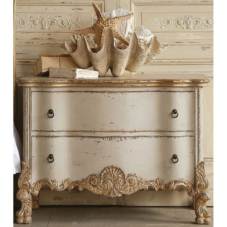 Eloquence® Roma commode in our Gold Two-Tone finish. A beautiful Italianate chest with ornate carvings, in a sandy beige base featuring gold leaf highlights. This commode is the perfect nightstand for your European bedroom. Enjoy the opulent style and an abundance of storage space!
