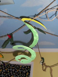 These are our paper plate snakes! The kids painted one side green and one side yellow. Then I cut them in a spiral, and added an eye and a tongue. We hung our snakes from our jungle vines!