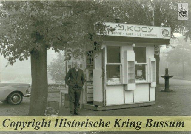 Amersfoortsestraatweg Tussen Burg. s'Jacoblaan en Huizerweg; achter de kiosk de Huizerweg. Kiosk van J. Kooy, verkoop van koffie-koek-ijs-limonade; in 1970 total loss gereden door een auto. Rechts de drinkfontein voor honden, paarden en vogels. Datum opname 1965.