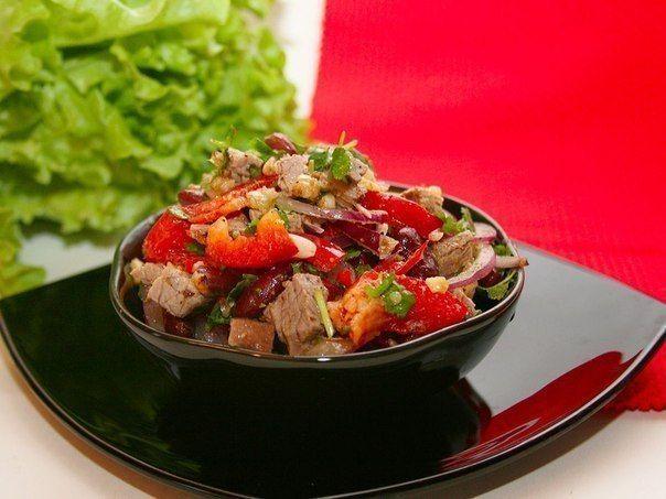 Вам потребуется: 1 банка красной фасоли 200-250 грамм отварной говядины (берем нежирный кусочек весом грамм 300, отвариваем в подсоленной воде час-полтора), 1 средняя красная луковица, 1 красный болгарский перец, половинка острого перца, 2-3 зубчика чеснока, 50 грамм грецких орехов, средний пучок кинзы, молотый черный перец, хмели-сунели. Для заправки: оливковое масло и винный уксус. Как готовить: 1. Лук режем тонкими полукольцами. Если лук