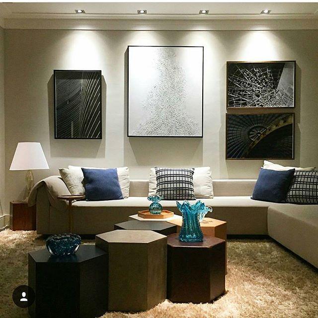 Sala de estar com gesso branco, paineis e quadros com spot, sofá bege e mesas de centro várias cores. tapete felpudo.
