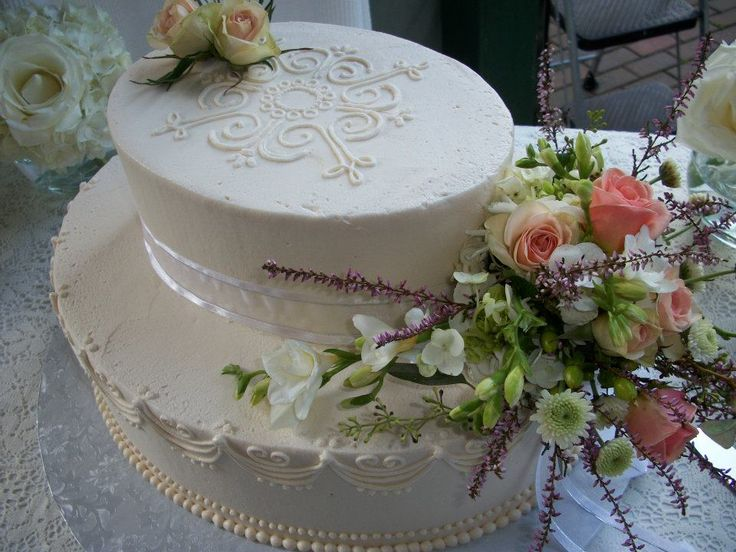 Elegant oval shaped wedding cake , with a very pretty detail done all in buttercream .