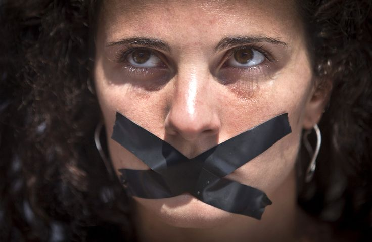 A member of the media sits with black tape across her mouth.Pentagon Legalizes Killing Journalists As 'Law Of War'