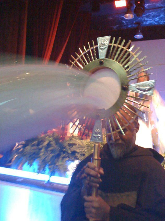 """Eucharistic Miracle. Photo taken on October 30th, 2011 during Adoration at Casa San Pablo in Sto. Dgo. Dominican Republic. The colors of red and blue/white=(Divine Mercy) and gold=(glory). These colors also feature on the Rosa Mystica statues (red, white and gold roses representing the mysteries of the Rosary etc). After careful examination, the """"gush"""" of graces (looking like water) are coming from the bottom area of the Host and over to the right, reminding us of the vision of Ezekiel."""