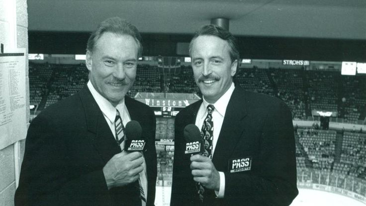 Pictured: Mickey Redmond and Dave Strader.  Dave Strader (1955-2017) passed away after battling a form of bile duct cancer on 1 October 2017.  Strader first served as a broadcaster for the Red Wings' American Hockey League affiliate in Adirondack from 1979-85 before beginning his 11-year tenure as the television broadcaster for Detroit.