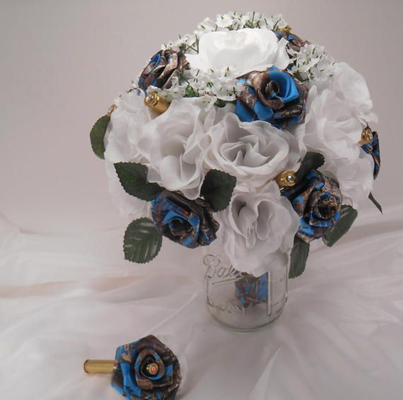 Blue Camo Wedding Bouquet, Blue Camo Bridal Bouquet, Blue True Timber, White Silk Flowers Flowers, Camo Wedding, Bullet Shells, Bridesmaid Let us create a bouquet for you that will last forever. THIS BOUQUET CAN BE MADE IN ANY COLOR FLOWERS WITH THE CAMO, This Wedding Bouquet, Bridal Bouquet is approximately 10 tall. Handmade Camo flowers sparkle in a silk arrangement with different orange silk flowers. The handle is covered with Camo. Brass Bullet Shells are added as an accessory.  This is…