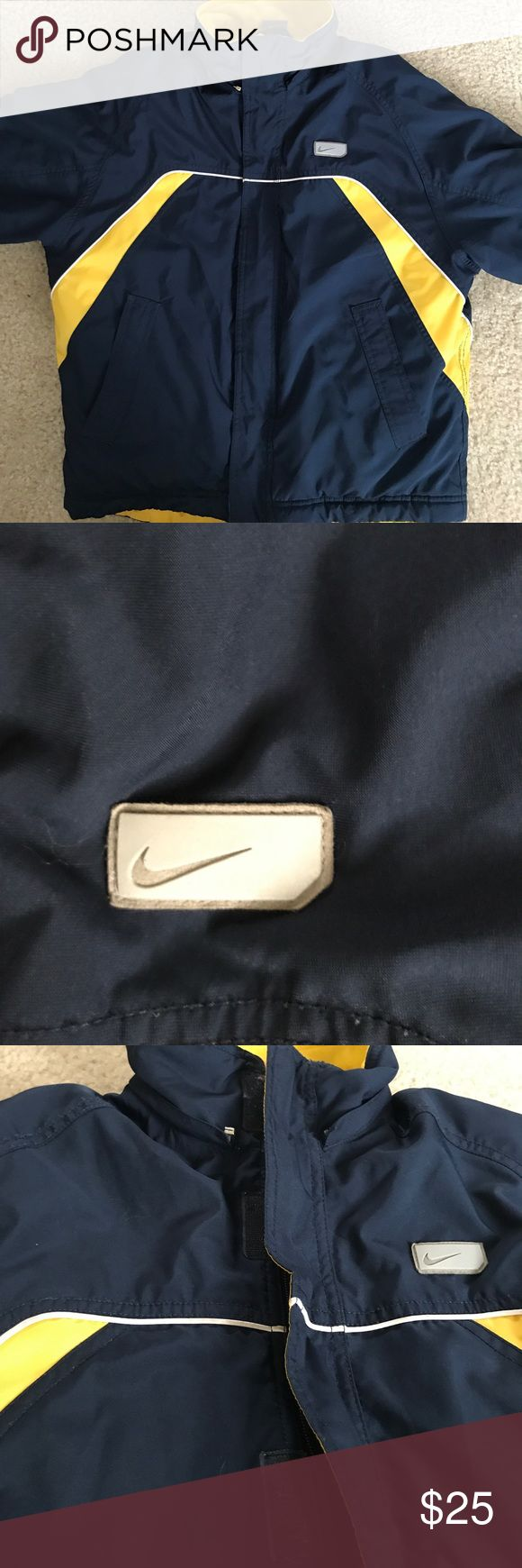 Nike Winter Coat Size S 8 Warm navy and yellow winter coat with white stripe and silver over Nike swoop logo on chest. NIKE on back. Velcro wrists. Zip-up with hidden velcro placket. Stain on back left bottom (shown). Other than that one stain EUC No fading. Just washed and hung up. Nike Size 8 Nike Jackets & Coats