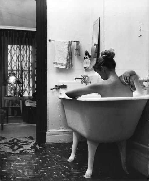 jo ann kemmerling reading a book while taking bath, new york • nina leen • 1954