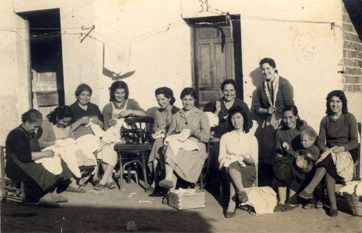 Barrio de Palomeras. Mujeres cosiendo en la puerta de la casa. 1960