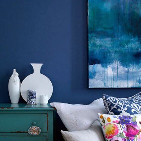 Blue walls and bright white bed and tourquois and yellow details for the spare bedroom.