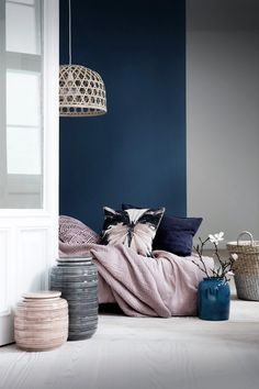 Cobolt blue wall and rose quartz decor. Pottery and wicker baskets add a tactile use of home accessories.