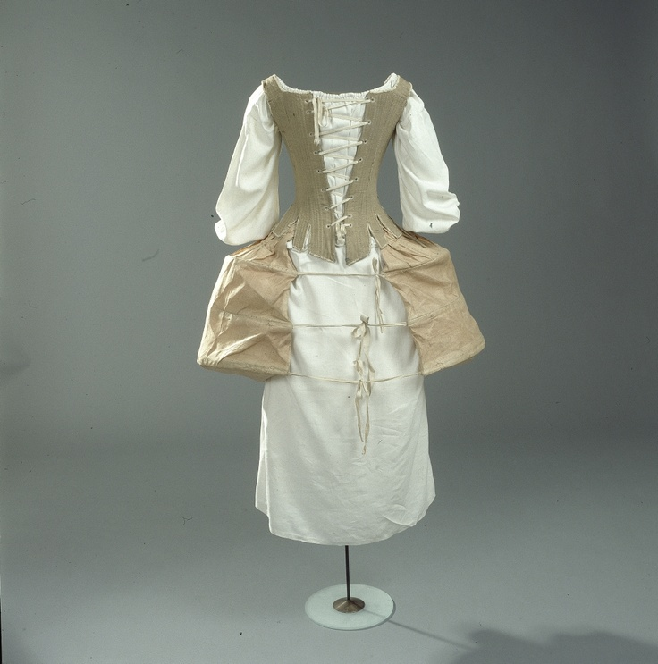 Hoftepocher og korset giver tidens smalle talje, flade bryst og brede hofter, 1700-1790.    The poches and corset provided the small waist, flat chest and wide hips that were in fashion in 1770-1790.