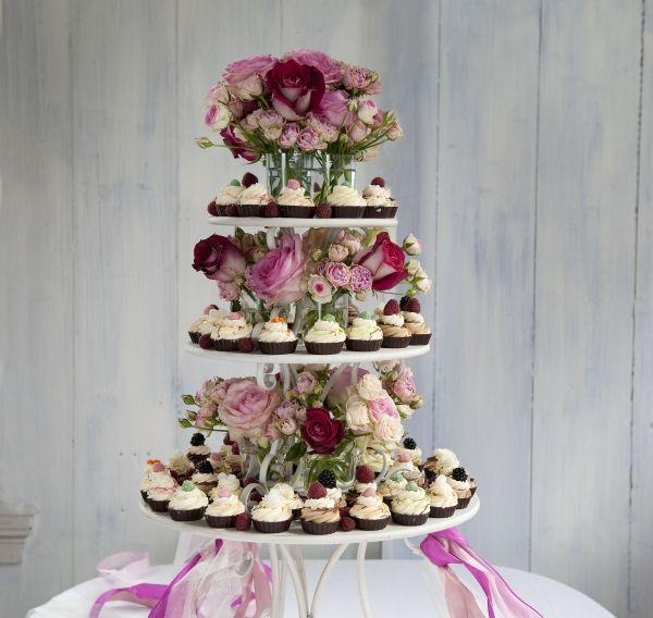 Aankleding bruidstaart met bloemen, origineel en sfeervol.