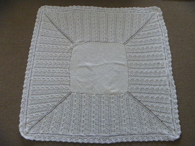 This is my last baby shawl I have recently knitted for my very good friend Kim.  It's a square patterned shawl with a square garter stitch insert in the middle with a lace edging.  It's knitted in 2ply merino baby wool all as one on circular needles except for the edging which is knitted on using straight needles.  This photo was taken while it was blocking and is extremely delicate!!