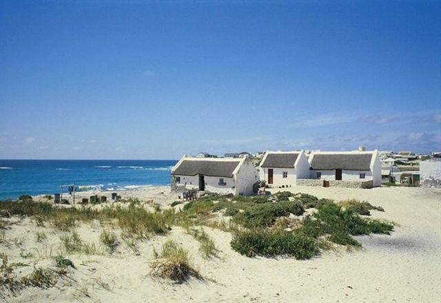 Arniston is locally known as Waenhuiskrans. Picturesque Waenhuiskrans is best known for its 200-year old restored fishermen's village, Kassiesbaai. This village, a national heritage site, with its whitewashed thatched cottages, has stolen the hearts of many an artist. The name Waenhuiskrans is derived from the big sea cave (waenhuis = wagon house). The town is also called Arniston after the East Indiaman Arniston wrecked nearby in 1815 with a tragic loss of 372 lives.