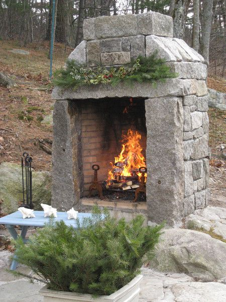 Custom natural wood outdoor fireplace built with a mix of reclaimed curbing and granite blocks.