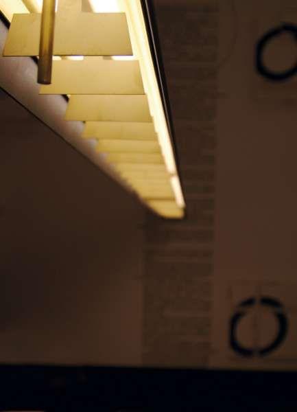 barra d'oro | Viabizzuno | barra d'oro | Viabizzuno | cuerpo iluminante en suspensión para interiores IP20 constituido por una estructura de acero pintado en antracita de 120x180x2400mm; disponible con cableado de lámparas fluorescentes tubulares de alta emisión T5 G5 4x54W HO 240V, y con fuente led lineal de alta eficiencia 3000K Ra90 182W 19680lm 240V. en todas las versiones lleva una óptica de láminas difusoras formada por aletas de latón natural arenado para un excelente confort visual.